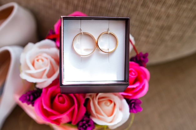 Golden wedding rings in a box and modern bouquet