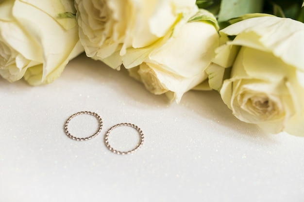 Golden wedding rings and fresh roses on white background