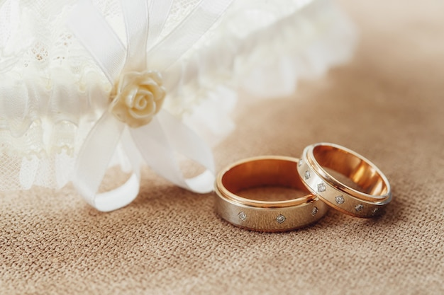 Golden wedding rings and garter of the bride, marriage concept