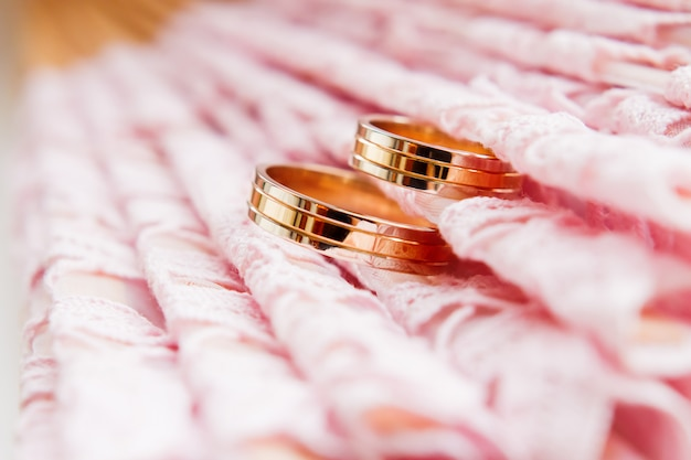 Golden wedding rings on lace pink fabric. wedding embroidery detail.
