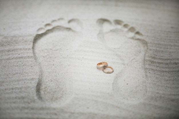 Золотые обручальные кольца лежат между шагами на пляже