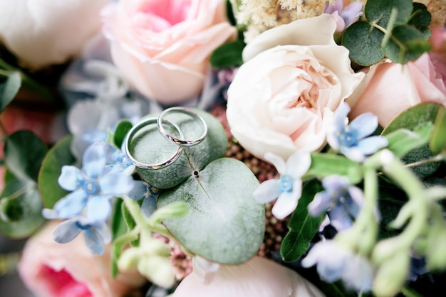 Golden wedding rings lie on the flowers in wedding bouquet