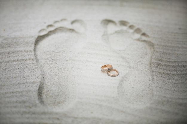 Golden wedding rings lie between footsteps on the beach
