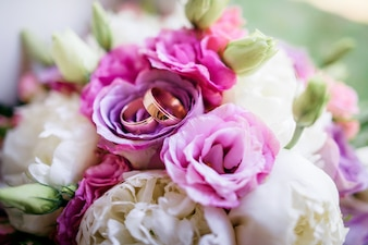Golden wedding rings lie on the colorful wedding bouquet made of roses and peonies