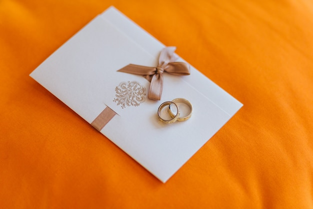 Golden wedding rings lie on white invitation card against orange background