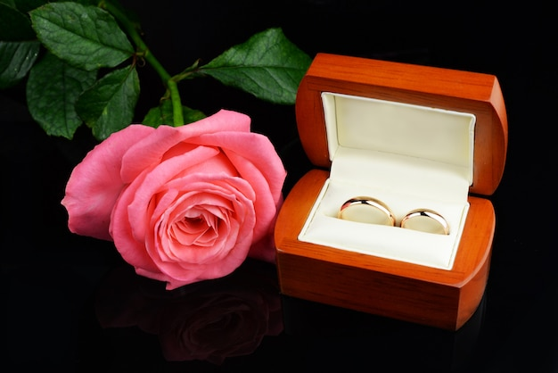 Golden wedding rings for newlyweds with a pink rose