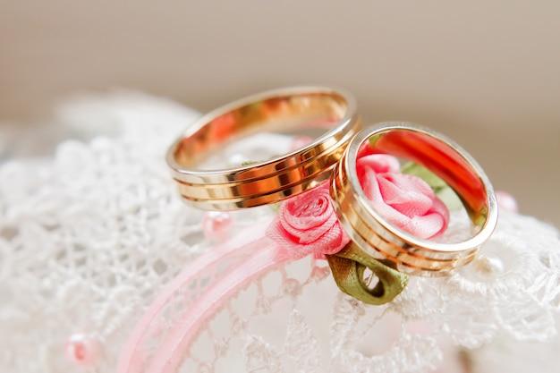 レースの白い布の上の黄金の結婚指輪