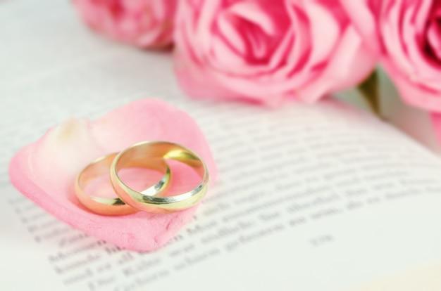 ピンクのバラ花びらと黄金の結婚指輪