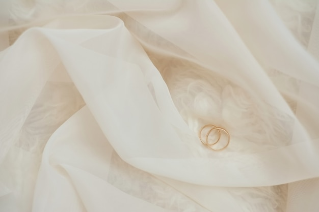 Golden wedding rings on pastel lace. shallow focus. bright background