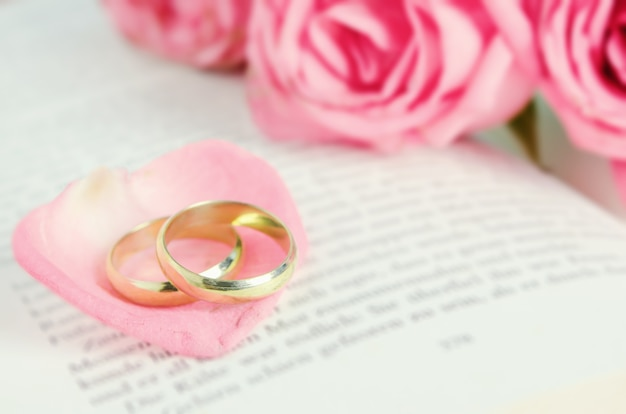 Golden wedding rings on pink rose petal with pink rose flower bouquet on open book