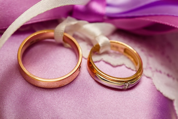 Golden wedding rings on the purple lace pillow. marriage concept