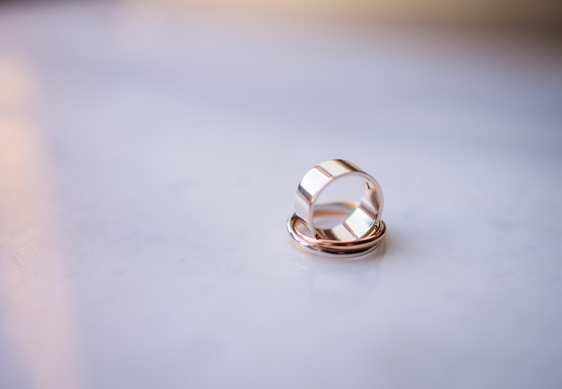 Golden wedding rings stand on each other on white marble table