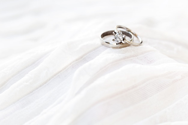Golden wedding rings with diamond lie onwhite fabric. symbol of love and marriage.