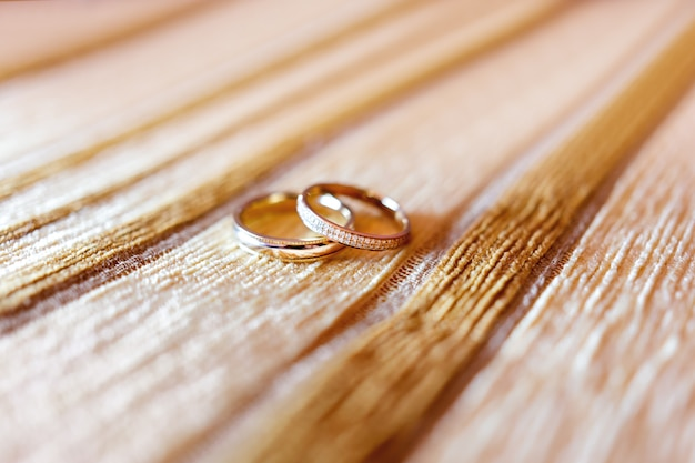 Golden wedding rings with diamonds on beige fabric background.