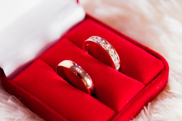 Golden wedding rings with diamonds in red gift box.