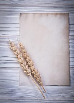 Золотое ухо пшеницы и чистый старинный бумажный лист на деревянной доске
