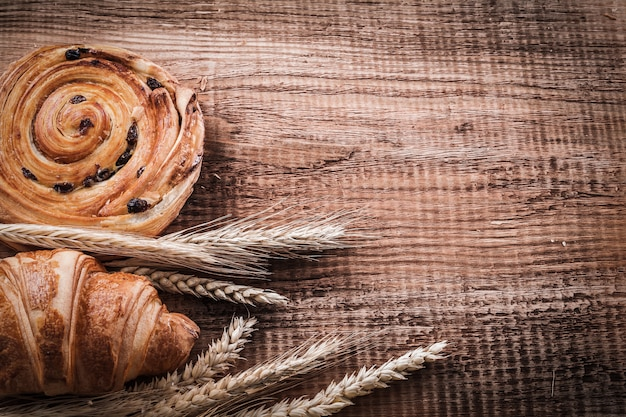 Golden wheat ears bun with raisins home-cooked croissant on oaken wooden board food and drink concept