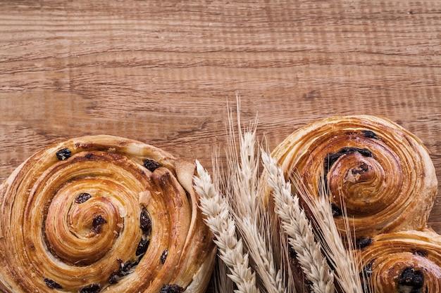 Golden wheat ears raisin bakery on oaken wooden board food and drink concept