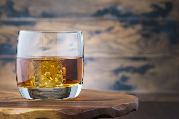 Золотой виски или бурбон с кубиками льда в стакане. на деревянном столе стакан с виски или бренди. алкогольный напиток