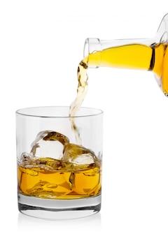 Золотой виски льется из бутылки в стакан со льдом