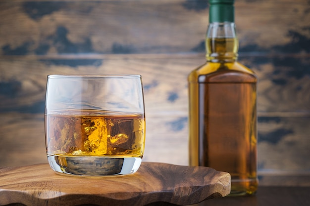 Golden whiskey witn ice cubes on wooden table with bourbon or scotch bottle. alcohol drink