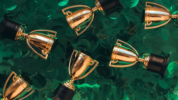 Golden winner cups on a green background. competitions concept.