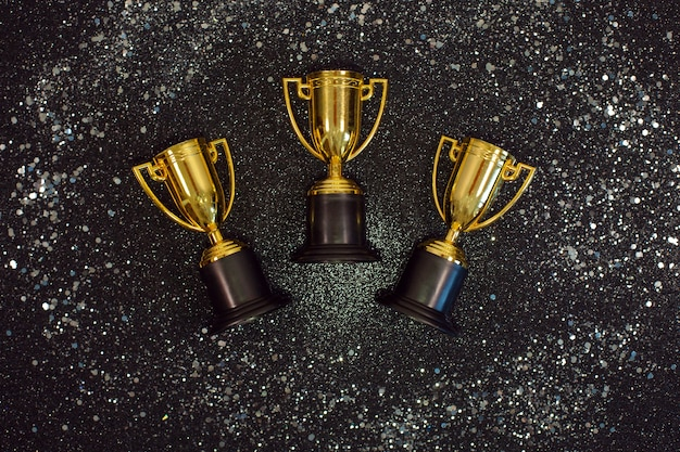 Golden winner cups with silver sparkles on a black desk