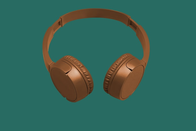 Golden wireless headphones on green background. flat style. design and colors