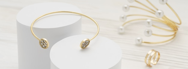 Golden with diamonds bracelet on white platforms and golden pearl bracelet and ring