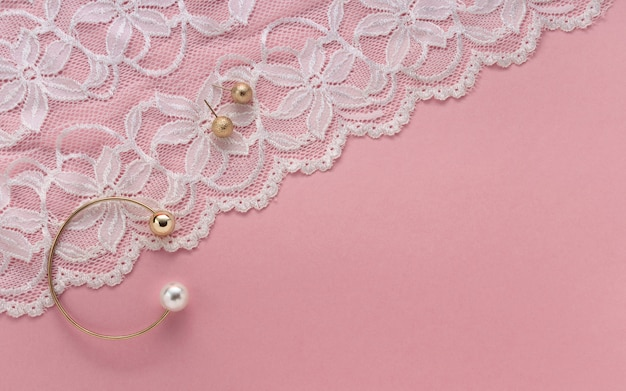 Golden with pearl bracelet and golden earrings on floral white textile on pink background with copy space