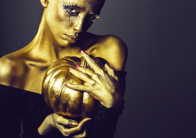 Golden woman with halloween pumpkin