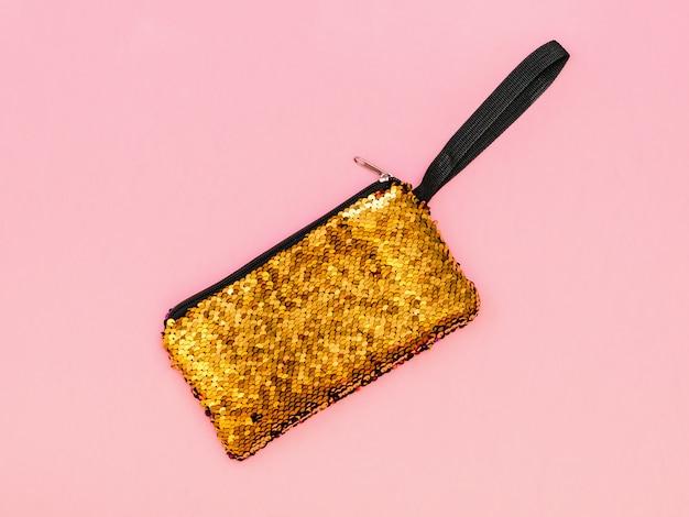 Golden women's handbag on a pink table