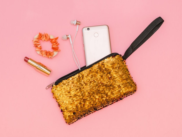 Golden women's handbag with phone and lipstick and bracelet on a pink table