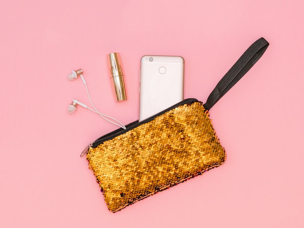 Golden women's handbag with phone and lipstick on a pink table