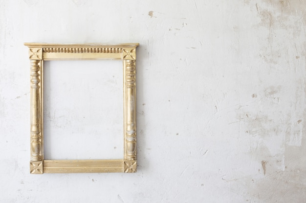 Golden wooden frame on old wall