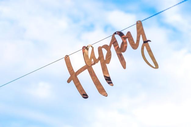 Золотое слово счастливый висит на гирлянде на фоне голубого неба с облаками.