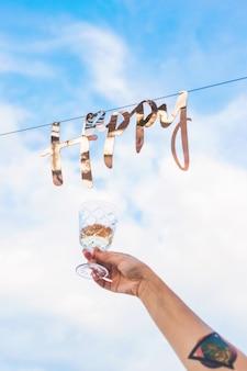 Золотое слово счастливый висит на гирлянде на фоне голубого неба с облаками рядом с рукой женщины