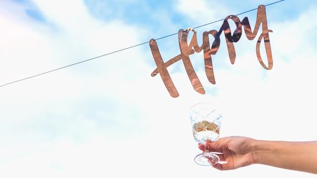 Золотое слово счастливый висит на гирлянде на фоне голубого неба с облаками