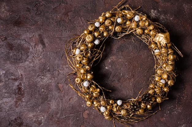 Золотой плетеный натуральный венок с желудями и сосновыми шишками на коричневой мраморной стене