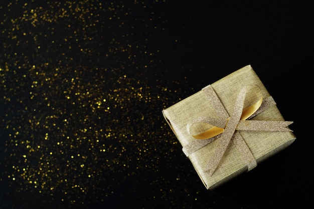 Golden wrapped gift box on black background.