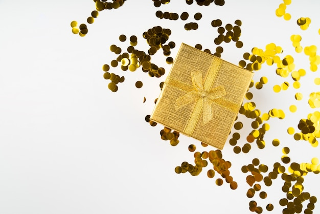 Golden wrapped gift surrounded by confetti