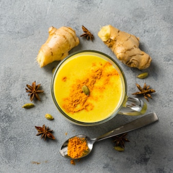 Golden yellow latte on light background. indian drink turmeric golden milk in glass. copy space top view