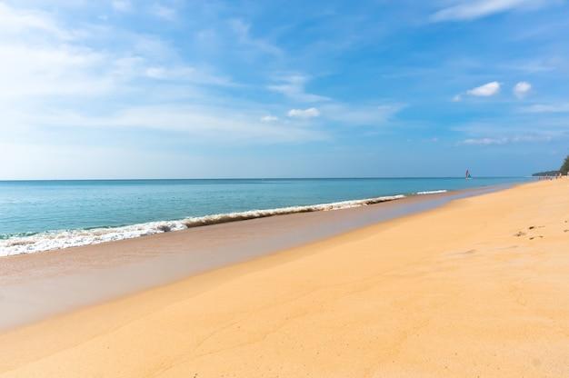 Золотисто-желтый песок на пустынном пляже у синего моря в яркий солнечный день. маленькая лодка плывет по морю на заднем плане