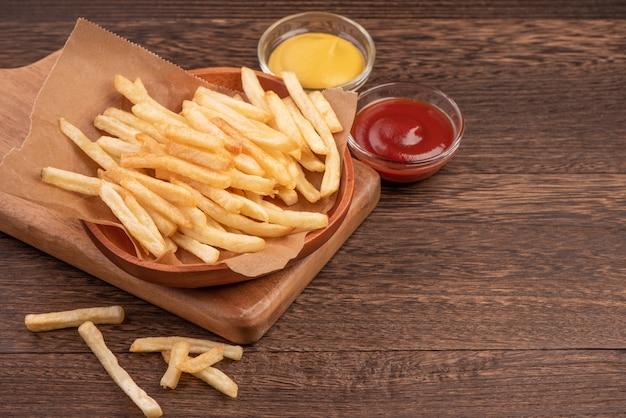 Золотой вкусный глубокий картофель фри на крафт-бумаге для выпечки и подносе для еды с кетчупом и желтой горчицей, крупный план, образ жизни.