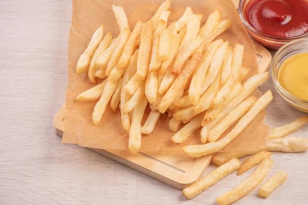 Золотой вкусный глубокий картофель фри на крафт-бумаге для выпечки и поднос для еды с кетчупом и желтой горчицей, вид сверху, образ жизни.