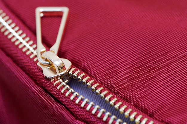 Golden zipper close up view. not fully buttoned metal zipper on backpack or clothes.