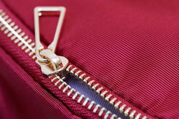 Золотая молния крупным планом. металлическая молния на рюкзаке или одежде не полностью застегивается.