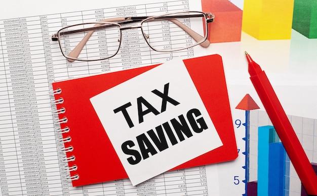 金縁のメガネ、赤いペン、カラーテーブル、デスクトップに「taxsaving」と書かれた白いカードが付いた赤いノート。ビジネスコンセプト。上からの眺め。