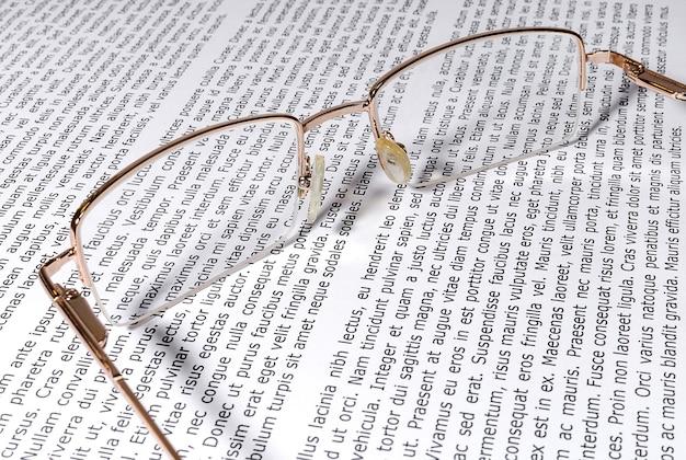 テキスト付きの紙に金縁の眼鏡トレーニングとドキュメントの操作