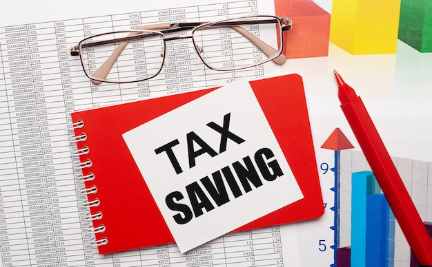 Goldrimmed glasses, a red pen, color tables and a red notebook with a white card with the text tax saving on the desktop. business concept. view from above.
